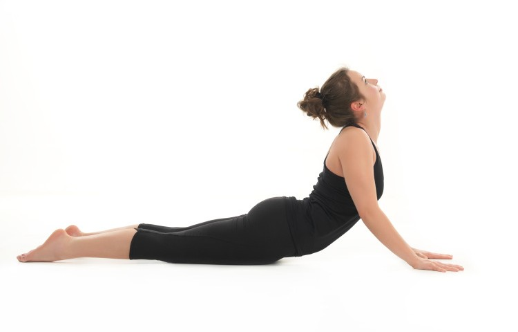 young woman demonstrating difficult yoga posture, full body side view, dressed in black, on white background